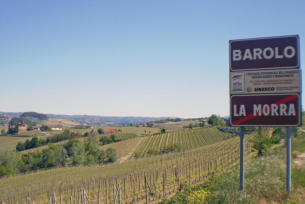 Il cartello Unesco in località Vergne di Barolo e, accanto alla zona boschiva, la cantina Sylla Sebaste con i vigneti di Nebbiolo da Barolo del cru San Pietro delle Viole. Sullo sfondo il Castello della Volta